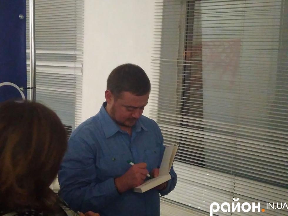 Андрій Анатолійович ставить автограф відданому шанувальнику